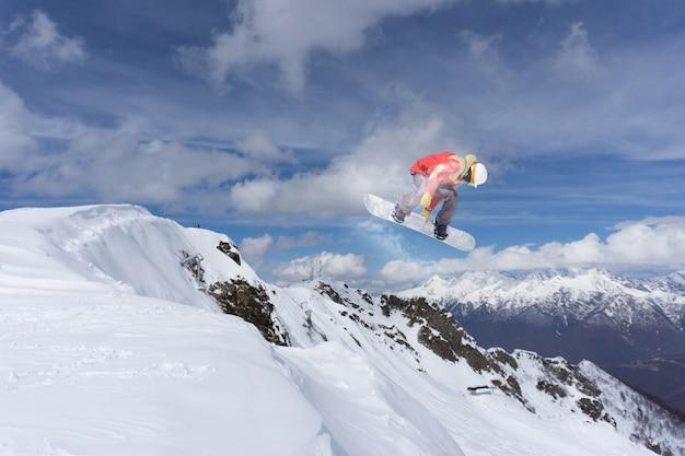 Fliegender snowboarder auf bergen.