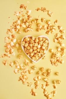 Fliegendes köstliches süßes popcorn mit karamell in weißer keramikherzplatte, lokalisiert auf trendfarbe gelbe tabelle.