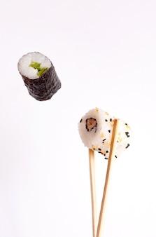 Fliegendes sushi auf weißem hintergrund, leckere sushi-rollen, avocado und essstäbchen