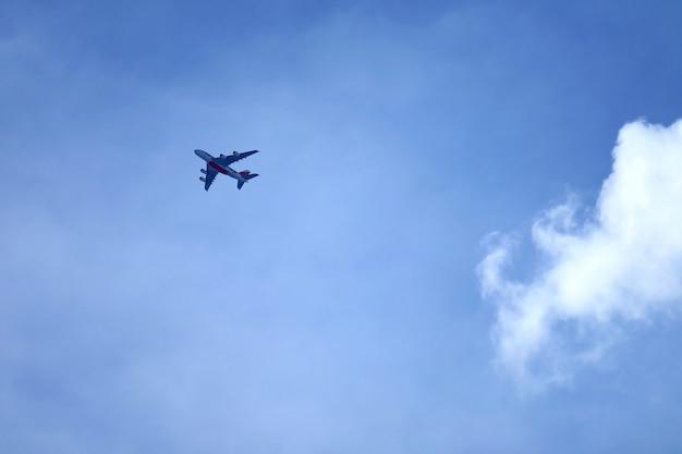 Fliegenflugzeug auf blauem himmel mit reinweißkumuluswolke