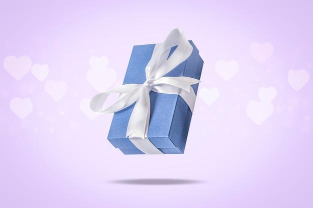 Fliegengeschenkbox auf einer hellen oberfläche mit herz formte bokeh. feiertagskonzept, geschenk, verkauf, hochzeit und geburtstag. .