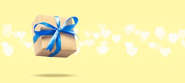 Fliegengeschenkbox auf heller gelber oberfläche mit herz formte bokeh. feiertagskonzept, geschenk, verkauf, hochzeit und geburtstag. .