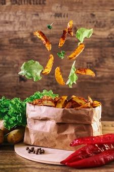 Fliegenscheiben der ofenkartoffel auf hölzernem hintergrund. kopfsalat, paprika, petersilie. fast food.