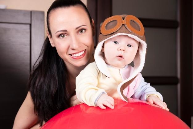 Fliegerkind, in einem pilotenhut, zusammen mit einer schönen jungen mutter, nahaufnahmeporträt.
