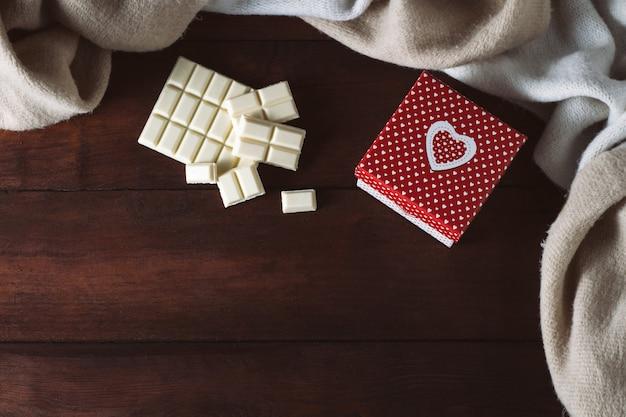Fliese der weißen schokolade, schal, geschenk auf einer dunklen holzoberfläche. kopieren sie platz. flachgelegt, draufsicht