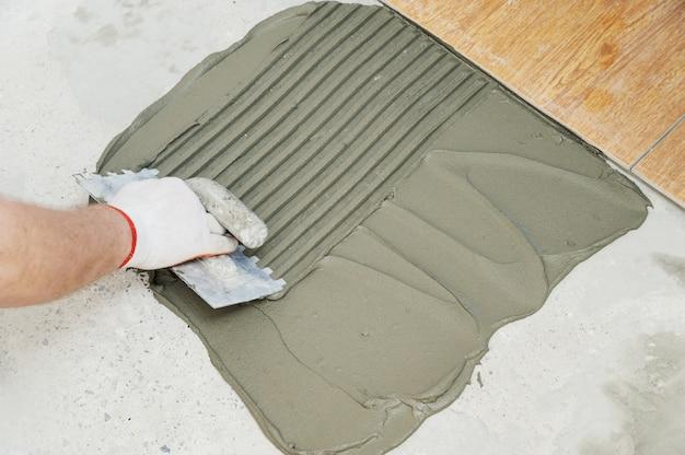 Fliesenlegerhand hält gekerbte kelle und kämmkleber zum verlegen der fliese