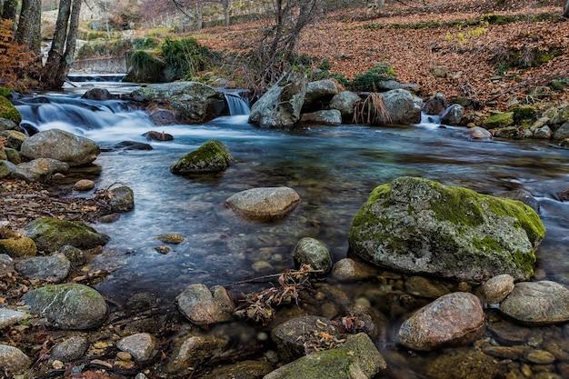 Fließender fluss durch die felsen und steine