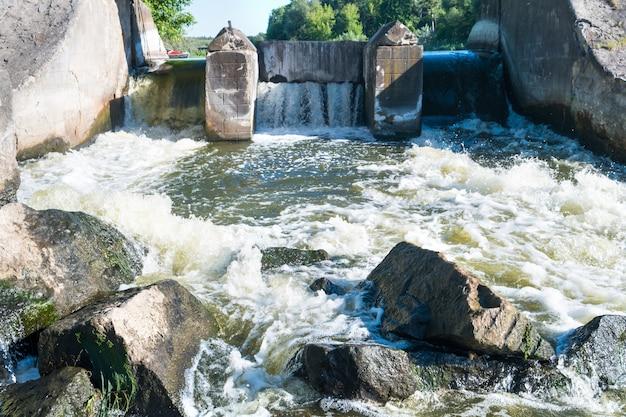 Fließendes flusswasser in der nähe eines damms mit großen felsen und einem strom, der durch sie rauscht