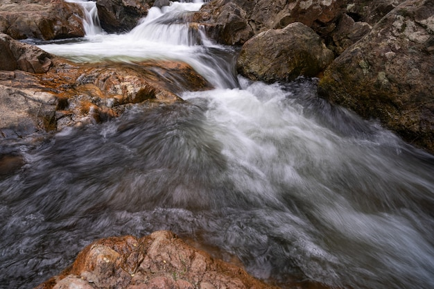 Fließendes wasser in wasserfallstromfelsen fließt.