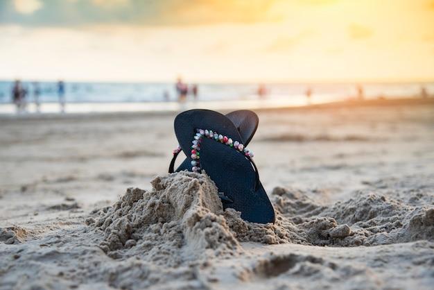 Flip flops am strand mit sandstrand sonnenuntergang und meer ozean hintergrund