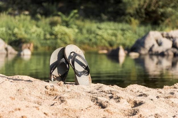 Flip flops auf sandküste in der nähe von wasser