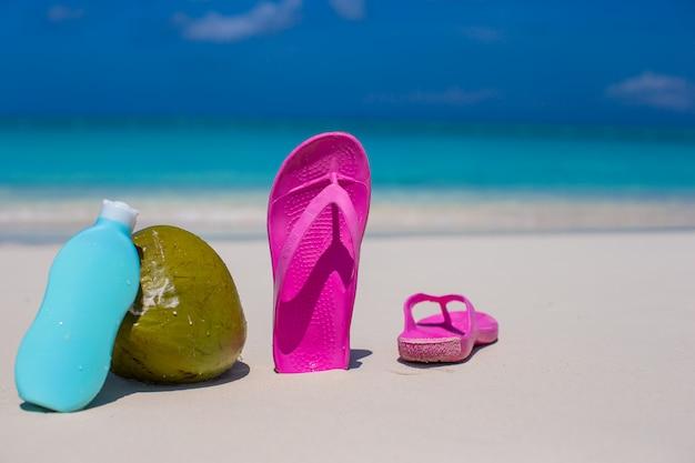Flip flops, kokos und sonnencreme auf weißem sand