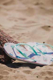 Flip flops mit eiscreme zeichnungen auf dem sand