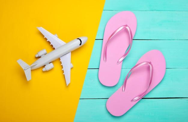 Flip flops und flugzeug auf einem gelben, blauen holz, reisen
