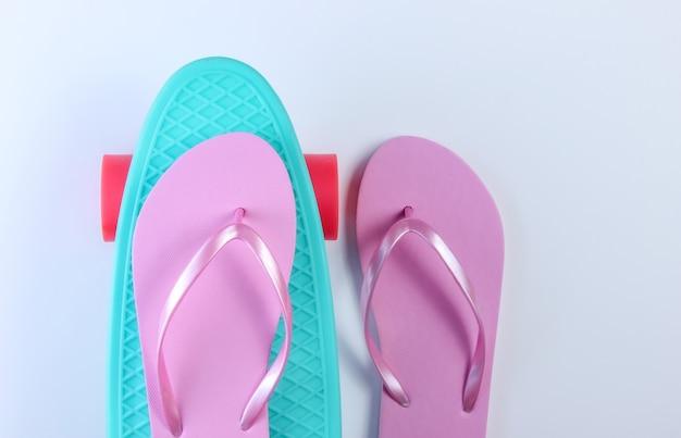 Flip flops und plastik mini cruiser board auf weißem hintergrund. sommerspaß. draufsicht