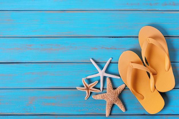 Flipflops starfish alter beunruhigter heller blauer strandholzhintergrund