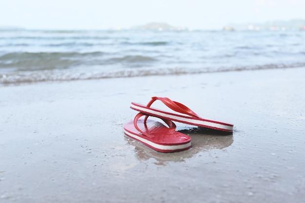 Flipflopstrand mit meer des sandigen strandes der welle