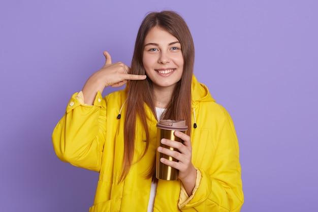 Flirten junge weibliche frau, die telefongeste tut, wie sagt, rufen sie mich isoliert über lila hintergrund zurück, hält thermobecher mit heißem getränk, schaut kamera lächelnd, tragend gelbe jacke.