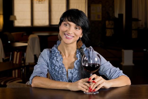 Flirtende frau, die an einer bar trinkt, die dreht, um einem anderen kunden ein großes einladendes lächeln zu geben