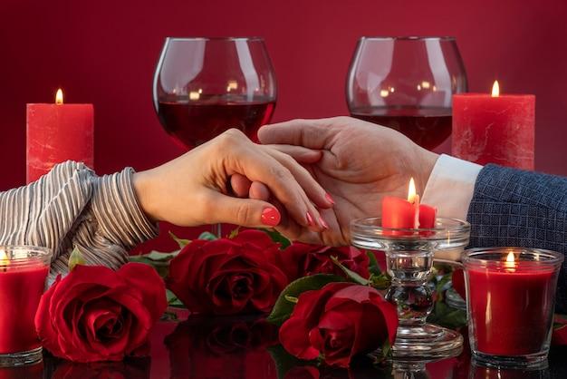 Flirtende männliche und weibliche hand unter schmelzenden kerzen galaabend valentinstag 14. februar