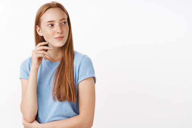 Flirty faszinierte und interessierte gut aussehende erwachsene rothaarige frau mit sommersprossen im blauen t-shirt, die sich mit leichtem sinnlichem lächeln nach rechts dreht und mit verlangen und zuneigung blinzelt