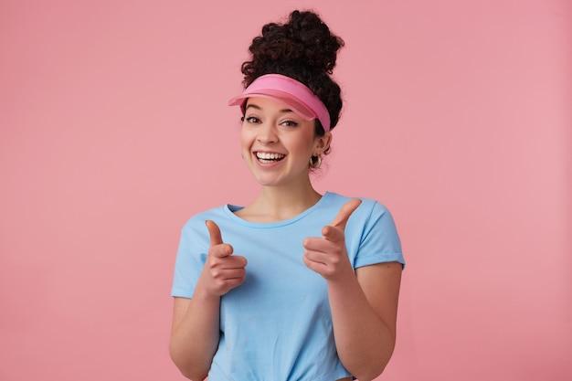 Flirty frau, schönes mädchen mit dunklem lockigem haar brötchen. trägt rosa visier, ohrringe und blaues t-shirt. hat sich geschminkt. zeige mit den fingern auf dich