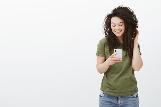 Flirty schöne lockige frau im dunkelgrünen t-shirt