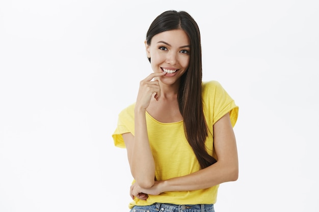 Flirty und sexy gut aussehende gebräunte frau mit langen dunklen haaren in gelbem t-shirt ohne make-up sinnlich lächelnd