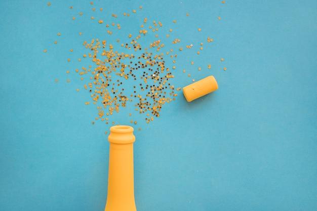 Flitter zerstreut von der flasche auf dem tisch