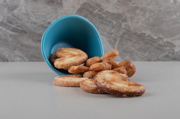 Flockige kekse, die aus einer schüssel auf marmorhintergrund verschütten.