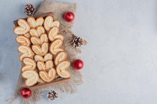 Flockige kekse in einem holzkorb gestapelt und mit weihnachtsschmuck auf marmoroberfläche umgeben