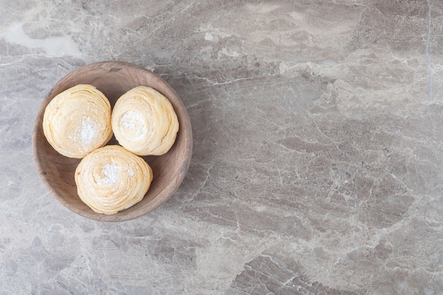 Flockige kekse in einer kleinen schüssel auf marmoroberfläche