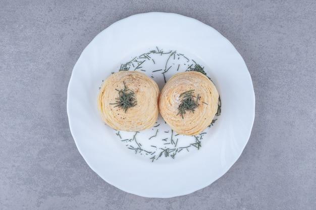 Flockige kuchen auf einer platte mit kiefernblättern auf marmortisch.