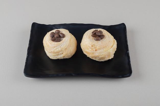 Flockige kuchen mit kaffeebohnenbelag auf einer platte auf marmorhintergrund.