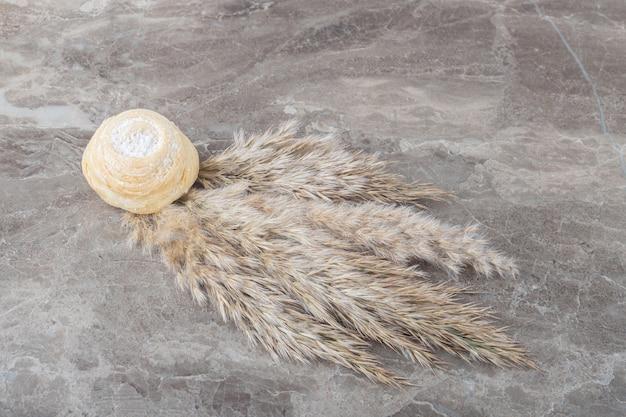 Flockiger keks und ein bündel nadelgrasstiele auf marmoroberfläche