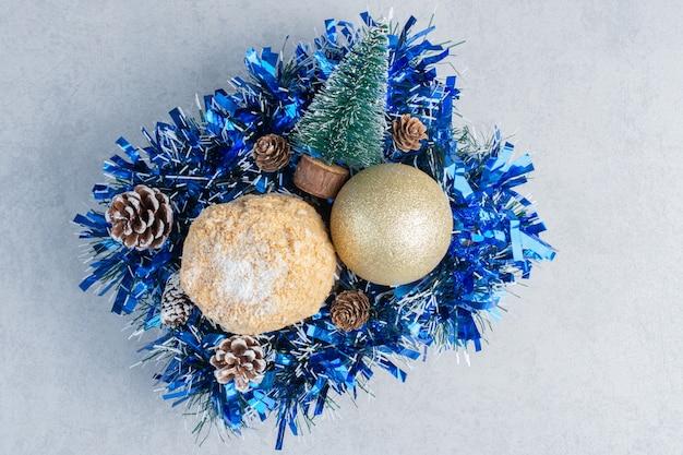 Flockiger kuchen, verschachtelt auf einem bündel von weihnachtsdekorationen auf marmoroberfläche