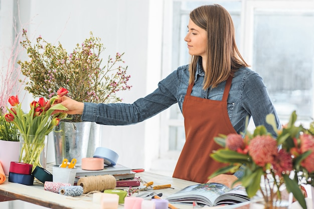 Florist bei der arbeit: das junge mädchen macht einen modernen blumenstrauß aus verschiedenen blumen