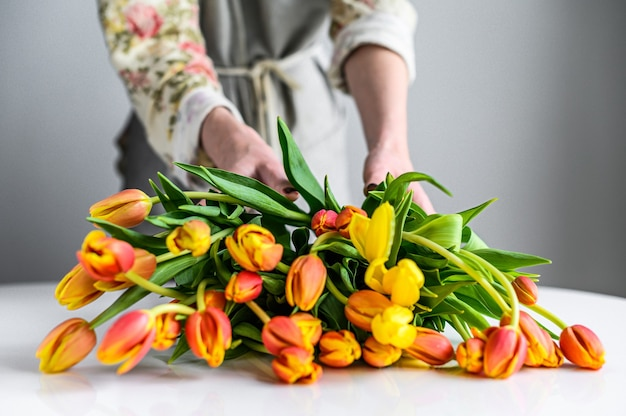 Florist bei der arbeit, der blumenstrauß der frühlingstulpenblumen macht