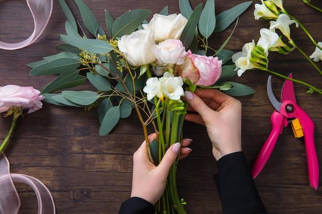 Florist bei der arbeit frau, die mode modernen blumenstrauß von verschiedenen blumen auf holzoberfläche macht
