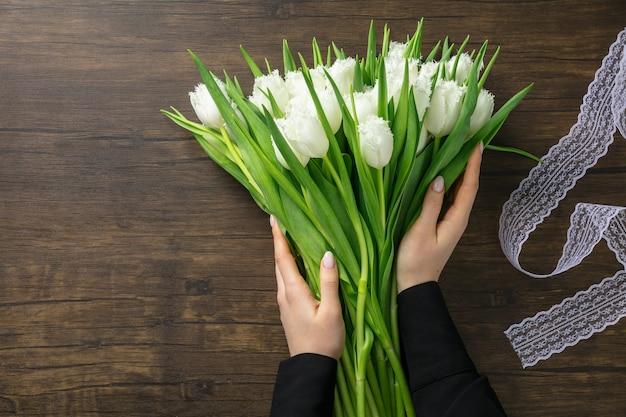 Florist bei der arbeit: frau, die modernen blumenstrauß der mode der verschiedenen blumen auf hölzernem hintergrund macht. meisterklasse. geschenk für die braut zur hochzeit, muttertag, frauentag. romantischer frühling. reinweiße tulpen.