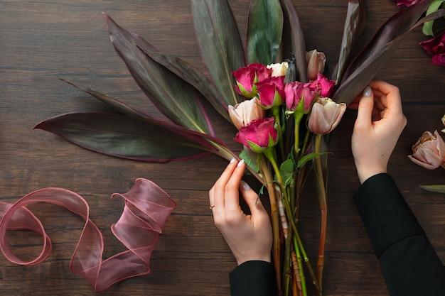 Florist bei der arbeit: frau, die modernen blumenstrauß der mode von verschiedenen blumen auf hölzernem hintergrund macht. meisterklasse. geschenk für braut auf hochzeit, mutter, frauentag. romantische frühlingsmode. passionsrosen.