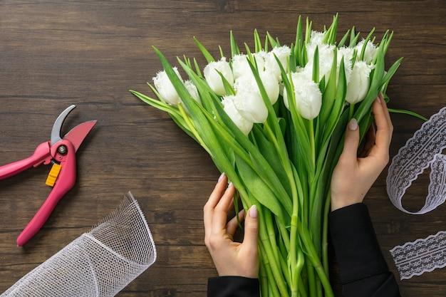 Florist bei der arbeit: frau, die modernen blumenstrauß der mode von verschiedenen blumen auf holzoberfläche macht.