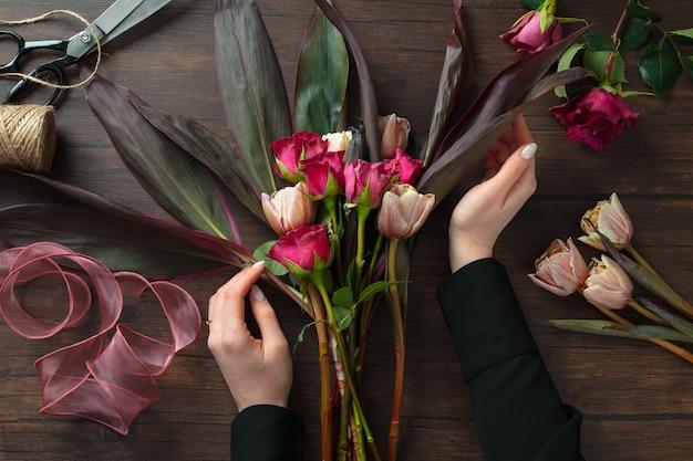 Florist bei der arbeit: frau macht modernen blumenstrauß aus verschiedenen blumen auf holzoberfläche. meisterklasse. geschenk für die braut zur hochzeit, muttertag, frauentag. romantische frühlingsmode. passionsrosen.
