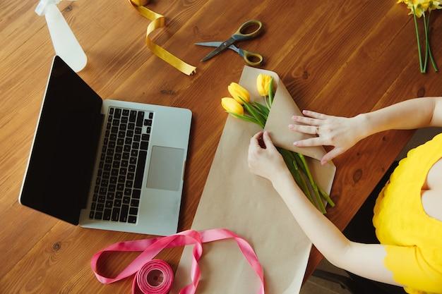 Florist bei der arbeit: frau zeigt, wie man blumenstrauß mit tulpen macht. junge kaukasische frau gibt online-workshop für geschenk, geschenk zum feiern. zu hause arbeiten, während isoliertes konzept unter quarantäne steht.