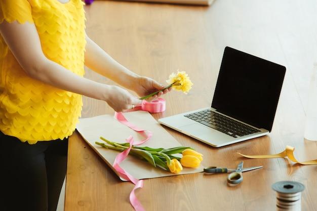 Florist bei der arbeit: frau zeigt, wie man blumenstrauß mit tulpen macht. junge kaukasische frau gibt online-workshop, um geschenk zu machen, geschenk zum feiern. zu hause arbeiten, während isoliertes, unter quarantäne gestelltes konzept.