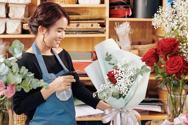 Florist besprüht bouquet mit spezieller flüssigkeit