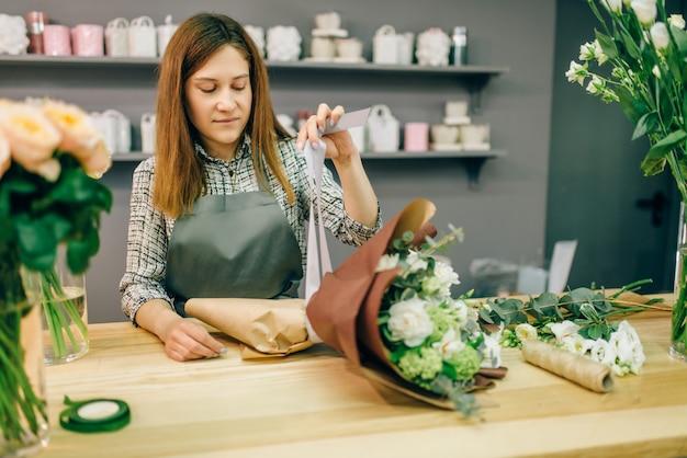 Florist bringt einen bogen zur frischen blumenkomposition an