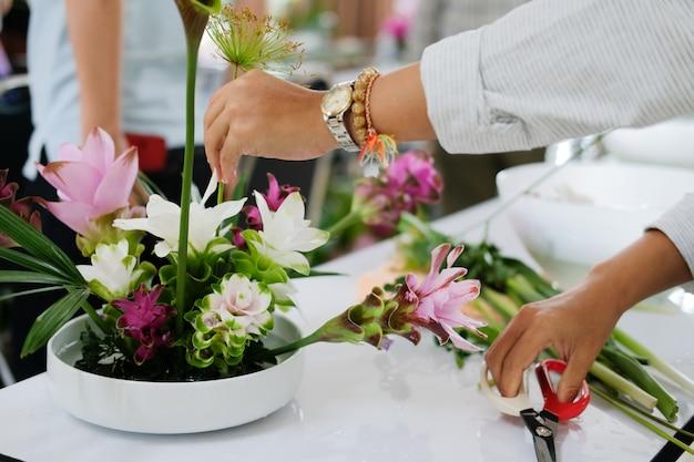 Florist, der blumenblumenstrauß im vase vereinbart.