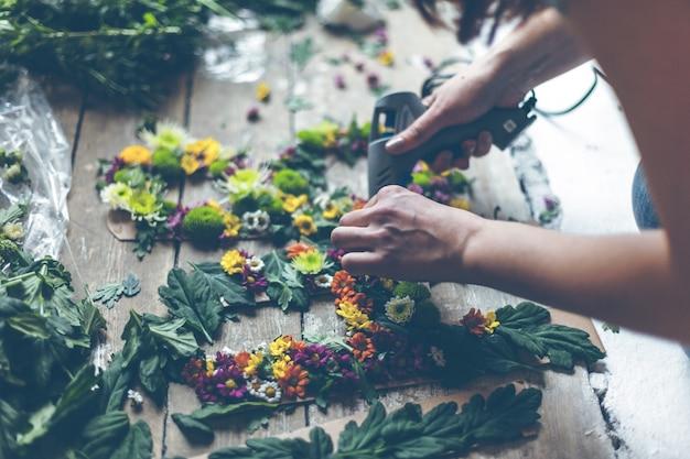 Florist, der blumendekoration mit buchstaben und kleber macht. natürliches licht in innenräumen mit geringer schärfentiefe