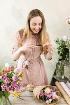 Florist, der blumenstrauß am telefon fotografiert. junge schöne floristen machen floristik mit rosa pfingstrose und wildblumen in der werkstatt auf holzhintergrund zusammenbauen. mobile-fotografie